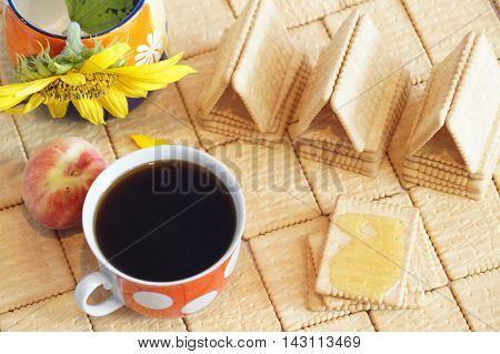 Sponge cake with honey. House crackers. Still crackers and a cup of black coffee. Red cup with white polka dots.