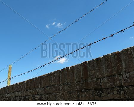 Barbed wire fence perspective useful as jail or lack of freedom concept