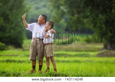 Happy child take a selfie in the cornfield asian