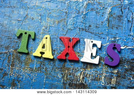 taxes text on colorful wooden letters. Wood abc at blue grunge background.