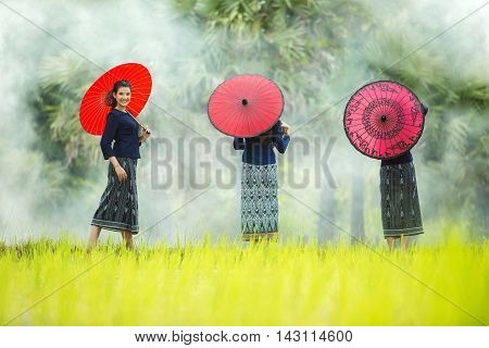 beautiful young woman holding a red umbrella, dressed in traditional concepts of culture and tourism promotion.