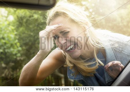 blond woman in the street looking inside a car being nosy