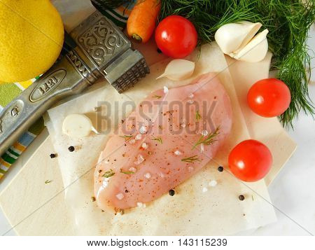 Chicken breast fillet with different spices on the kitchen table prepared for cooking.