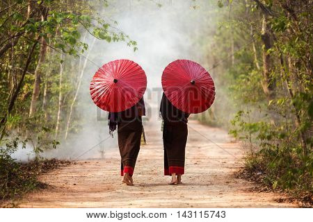 Two young women dressed in traditional red umbrella walking forward.