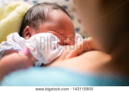 breastfeeding. mother holding newborn baby in an embrace and breastfeed