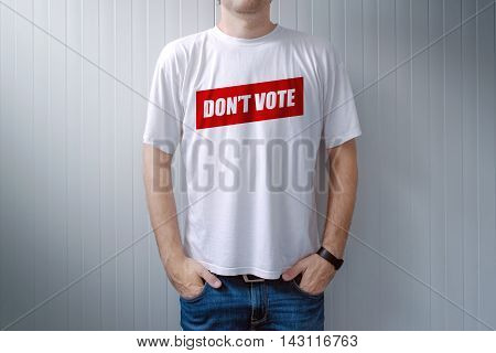 Handsome man wearing shirt with Don't vote title printed on chest express attitude and opinion on political elections