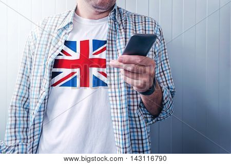 Handsome casual man with United kingdom flag printed on shirt using mobile phone concept of patriotism national pride and love for Great Britain