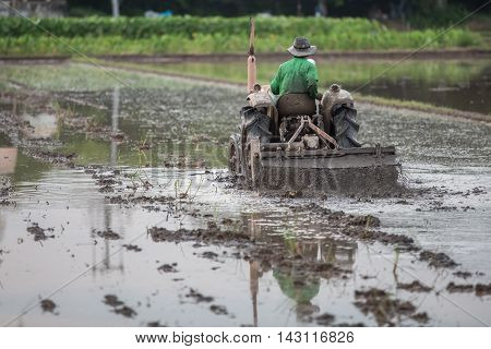 farmer sitting in a tractor during sunset time