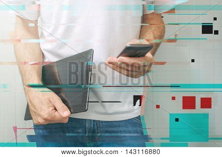 Guy using smartphone and digital tablet computer modern mobile electronic devices to access internet and social networks. Digital glitch effects were added in post production.