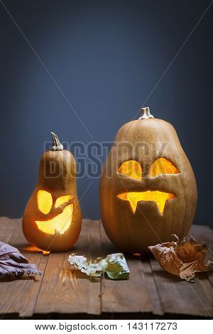 Jack o lanterns Halloween pumpkin face on wooden background and autumn leafs