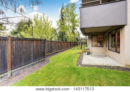 Fenced Backyard With Well Kept Lawn. Concrete Floor Porch An Backyard.