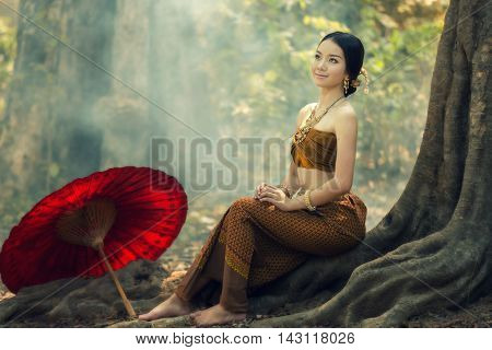 Thailand Girl in traditional costume sitting on tree roots.