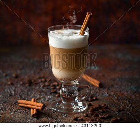 Coffee latte in a tall glass with stick of cinnamon