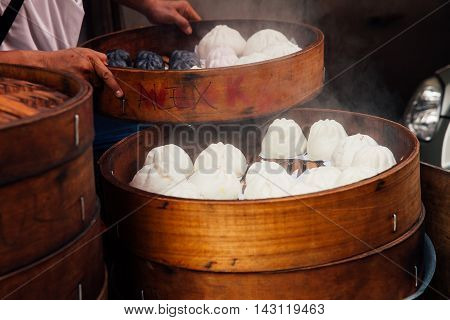 Man cooking chinese traditional steamed buns at the street food stall in Chinatown Kuala Lumpur Malaysia.