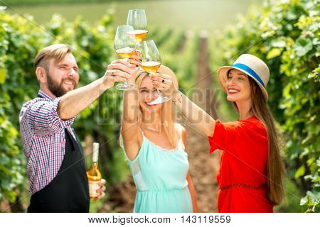 Young women with handsome wine maker having fun clinking glasses on the vineyard
