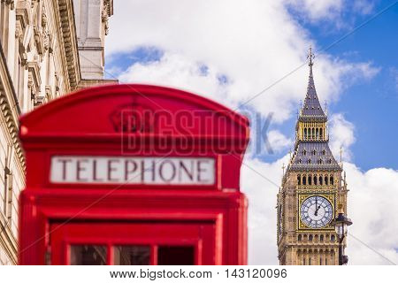 Traditional red british telephone box and Big Ben at the background with blue sky and clouds - London, UK