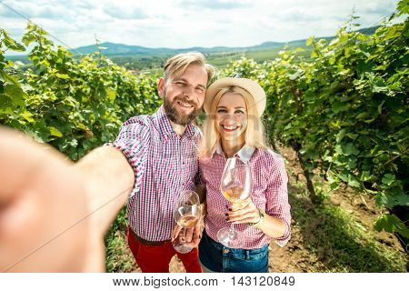 Beautiful caucasian couple in checkered shirts making selfie photo with glasses of wine on the vineyard. Green tourism at the winery