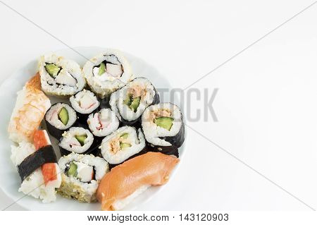 Plate of sushi, with soy sauce and chopsticks, white  background.