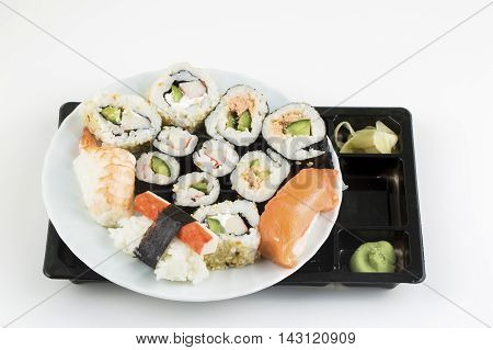 Plate of sushi, with soy sauce and chopsticks, over bamboo background.