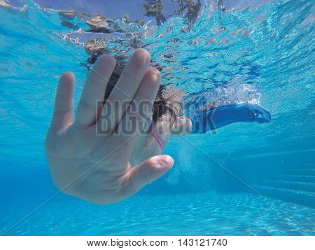 Unrecognizable brunette girl hiding face with palm hand while diving underwater in pool with arm in plaster