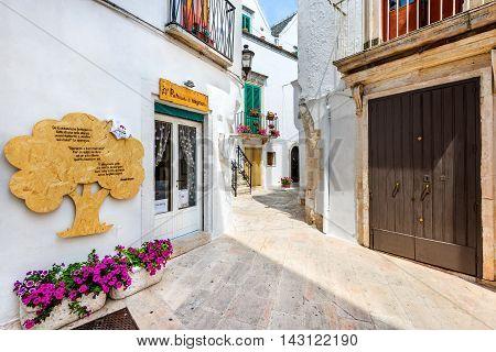 LOCORTONDO ITALY - 10 JULY 2015: Medieval whitewashed street and houses in small city of Locorotondo Puglia in Bari region.
