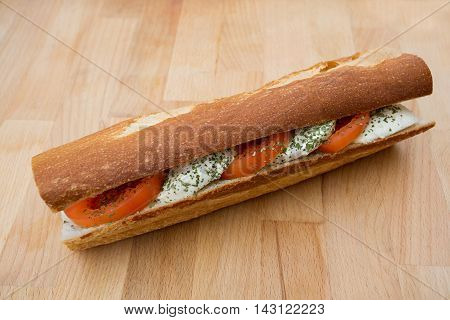 A sandwich with mozzarella and tomatoes on a wooden board