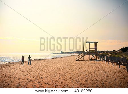 Couple walking along the beach at sunset. Idyllic beach scene.