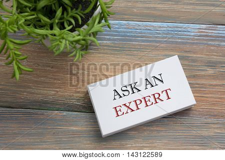 Ask an expert. Business card with message. Office supplies on desk table top view