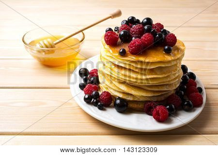 Homemade pancakes with honey and fresh berries. Stack of breakfast pancakes served with blueberry raspberry and blackcurrant.