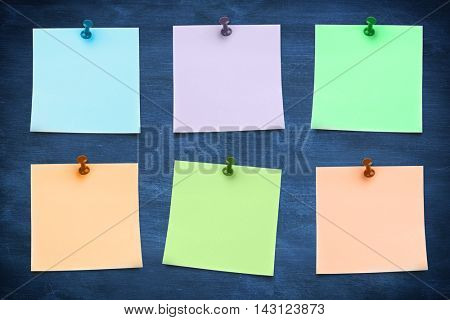 Blue sticky note with thumbtack against blue chalkboard