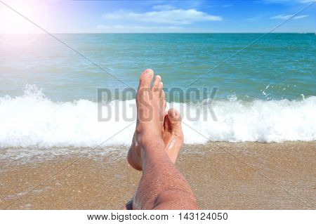 feet on the background of sea and blue sky with clouds