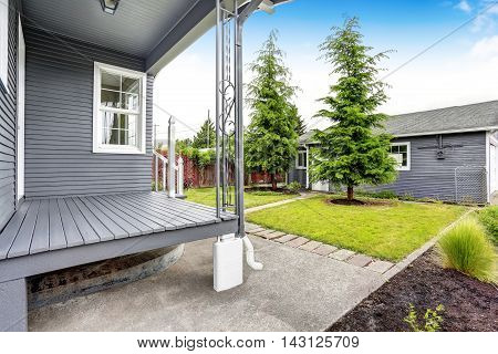 Backyard House With Siding Trim, Wooden Floor Porch, Concrete Walkway.