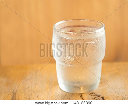Glass off water place on wooden table.