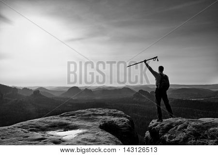 Tourist With Poles In Hands Stand On Rock Watching  For Next Step. Sunny Spring