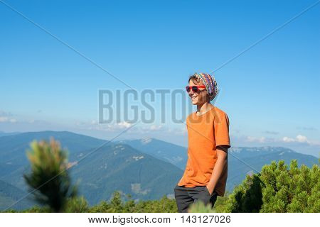 Smiling young hiker in sunglasses standing on the background of the mountains in sunny day.