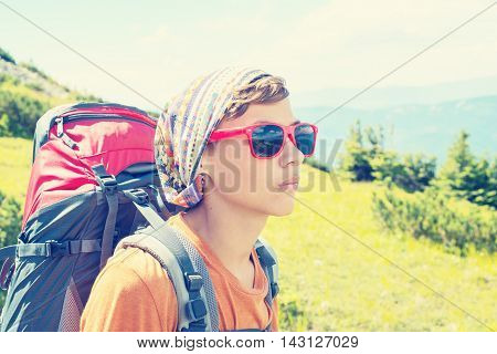 Portrait of the young hiker in sunglases with backpack on the background of mountains. Toned image.