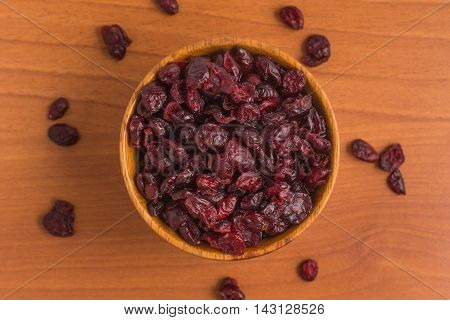 Dried Cranberries into a bowl over a wooden table
