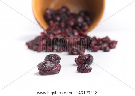 Dried Cranberries into a spoon over a white background
