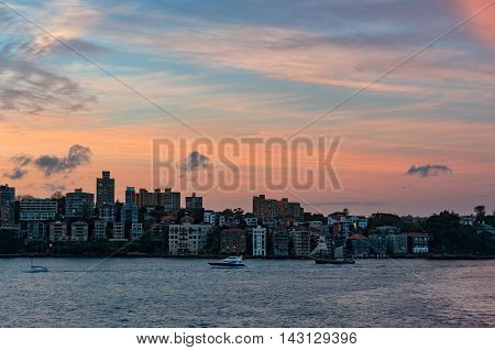 Cityscape with dramatic colorful evening sky on the background. Modern waterfront buildings of Kirribilli suburb of North Sydney Australia. Urban sunset landscape with space for text