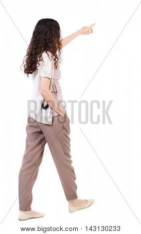 back view of pointing walking  woman. going girl pointing.  backside view of person.  Rear view people collection. Isolated over white background. Long-haired curly girl is putting his hand in his
