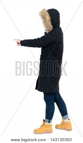 Back view of  pointing young women in parka. Young girl gesture. Rear view people collection.  backside view of person.  Isolated over white background. The girl in warm winter jacket is black with