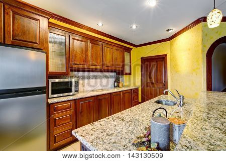 Beautiful Cherry Wood Kitchen With Marble Counters And Tile Floor.