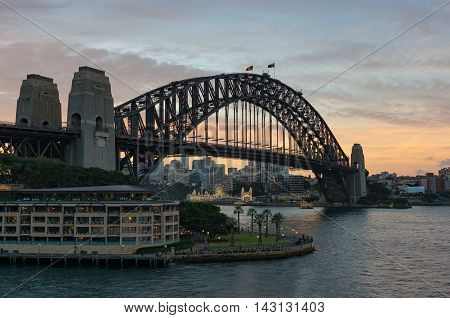Circular Quay and Harbour Bridge with view of North Sydney and sunset sky on the background