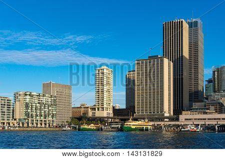 Modern skyscrapers with railway train station and ferry wharfs against blue sky on the background. Circular Quay Sydney Australia
