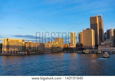 Modern skyscrapers with railway train station and ferry wharfs on sunset. Circular Quay Sydney Australia