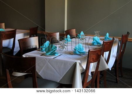 Long tables covered with cloth and set for dinner, with glasses and  pretty blue napkins that welcome guests to come in and relax over a shared meal.
