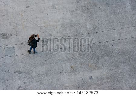Sydney Australia - Jul 10 2016: Aerial view of young woman taking photo of something with her smartphone. Gadgets in everyday life concept. International terminal square