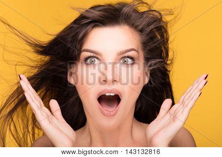 Portrait Of Brunette Girl On Yellow Background.