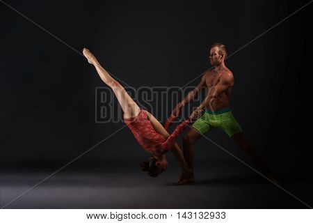 Couple of gymnasts performing trick at camera, on gray background