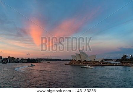 Sydney Australia - Jul 10 2016: Sydney Opera House at sunset. Iconic Sydney architectural sightseeing and water transport against colorful sky on the background. Circular Quay CBD